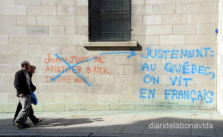 """En respuesta a una pintada en inglés (""""No seas un ladrillo más en la pared""""), podemos leer """"Precisamente: en Québec vivimos en francés"""""""